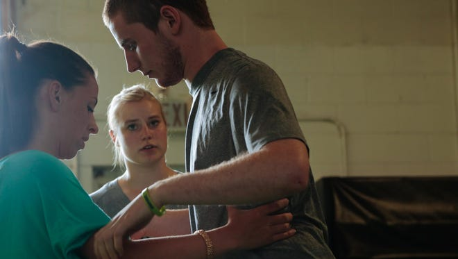 Chris Norton is assisted by his fiancee, Emily Summers, while walking toward his wheelchair as assistant strength and conditioning coach Megan Sundstrom (background) monitors during rehabilitation at Barwis Methods in Plymouth on June 5, 2015. Norton broke his neck in a college football game in 2010 while playing at Luther College. He was given a three percent chance to walk again but has worked and gritted through and can walk with minor assistance. Norton and his fiancee moved to Michigan to work at Barwis Methods in Plymouth to continue his recovery.