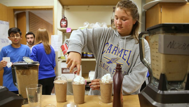 Junior Hannah Radde, 16, adds whip cream to frappucinos at the Carmel Cafe and Market run by DECA students at Carmel High School, Thursday, May 4, 2017. Students have been self-running the coffee shop and spirit-wear business for three years, based on a plan designed for class by two Carmel high alumni.
