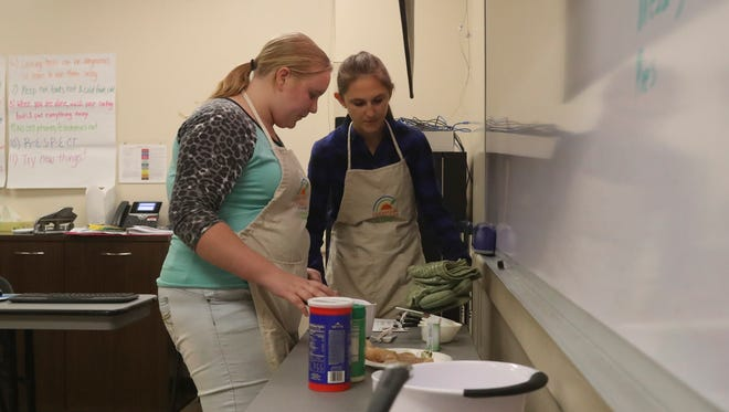 Student Rosemary Dougan-Ballard, 12, left, learns cooking tips from Shasta Community Health Center patient educator Betsy Amstutz at Thursday's after-school workshop.