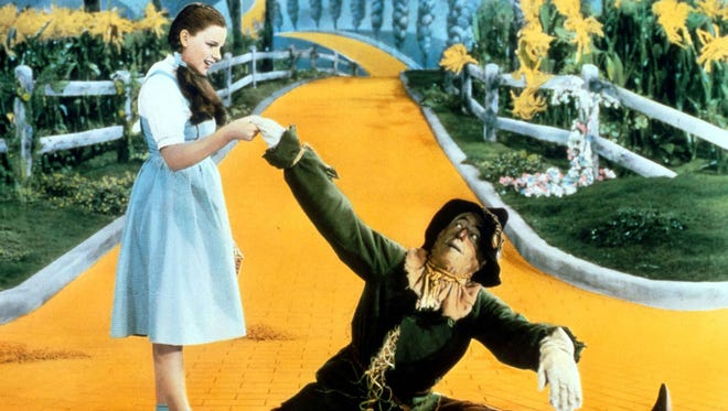 """Dorothy (Judy Garland) and her straw-stuffed friend the Scarecrow (Ray Bolger) begin their trip down the Yellow Brick Road. photos by MGMA scene from the 1939 classic """"The Wizard of Oz."""""""
