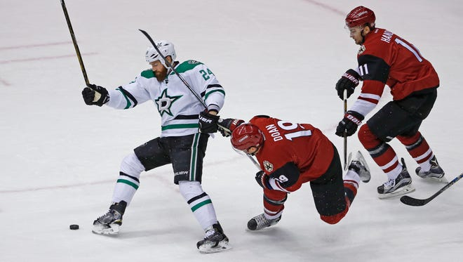 Coyotes' Shane Doan (19) and Stars' Jordie Benn (24) collide fighting for a puck in the first period at Gila River Arena in Glendale, Ariz. on Thursday, March 24, 2016.