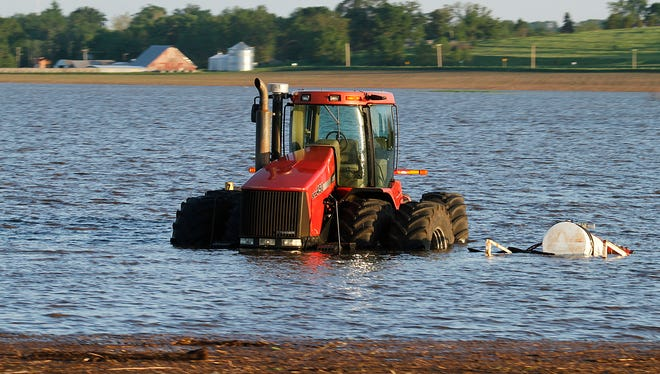 A tractor sits in very high water at a farm between Toledo and Marshalltown during flooding in 2013. BRYON HOULGRAVE/REGISTER FILE PHOTO