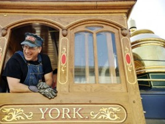 Head engineer Steve Meola leans out the cabin window of York No. 17 to share a joke with Dave Kloke, who built the engine, in May. Meola is head engineer for Steam Into History, Inc. York No. 17, a steam-engine replica of a Civil War-era train. (DAILY RECORD/SUNDAY NEWS -- FILE)