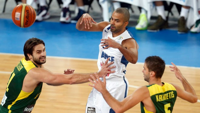 France point guard Tony Parker throws a pass over the defense of Lithuania's Mantas  Kalnietis, right, during the Eurobasket 2013 title game.