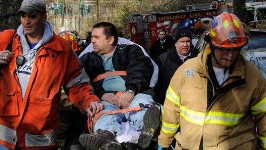 n this photo taken on Sunday, Dec. 1, 2013, Metro North Railroad engineer William Rockefeller is wheeled on a stretcher away from the area where the commuter train he was operating derailed in the Bronx borough of New York.