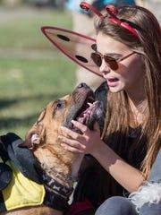 Mya Montgomery, 16, pets her dog, Deeoughee as they