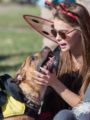 Mya Montgomery, 16, pets her dog, Deeoughee as they