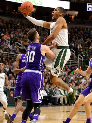 Senior guard Alvin Ellis gets hit in the groin as he leaps toward the basket during Friday night's game at Breslin. MSU beat Northwestern, 61-52. Ellis finished with a team-high 16 points.
