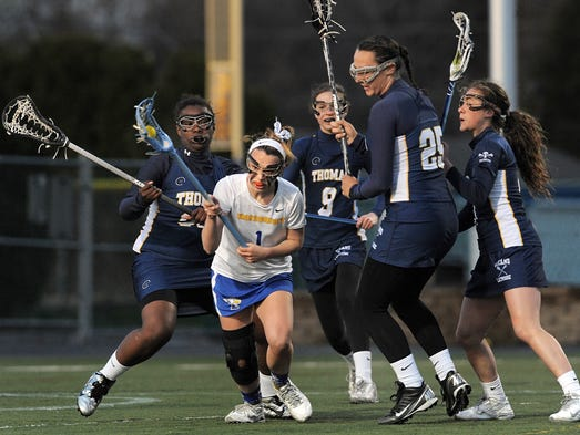 Irondequoit's Meghan Vadala, second from left, spins away from the pressure of a group of Webster Thomas during the Titans' 7-6 win.