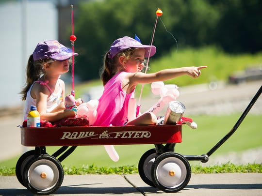 Twin sisters Mila Thompson, (left), and Jordan Thompson, 4, of Henderson, sit in a wagon before participating in the fishing contest during Henderson's Come on Down to the River event at Audubon Mill Park, in Henderson last year.