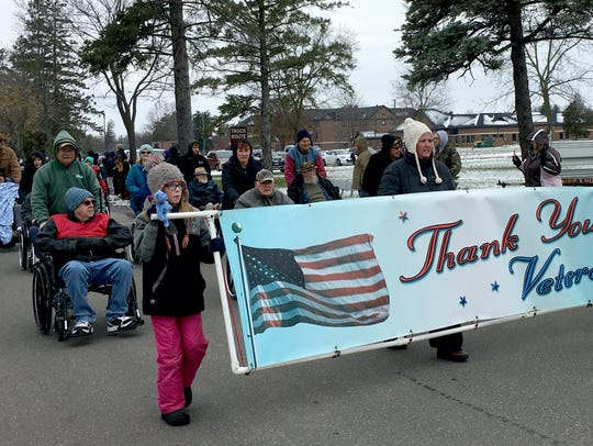 A crowd cheered on veterans as they marched in the