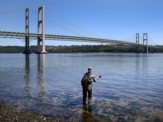 A fisherman casts his line near the two Tacoma Narrows