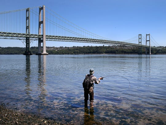 A fisherman casts his line near the two Tacoma Narrows Bridges. The old bridge, farther away in this picture, takes drivers toward Gig Harbor. The newer bridge, which opened 10 years ago, takes drivers toward Tacoma.