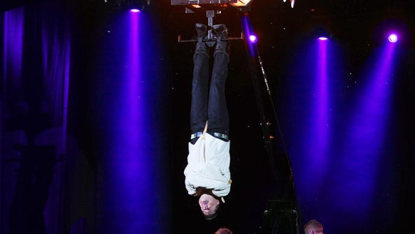 Illusionist Jay Owenhouse hangs upside down, ready