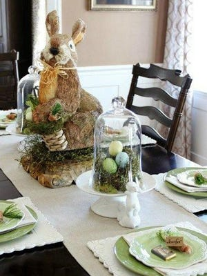 A large sisal and jute bunny makes an adorable centerpiece for this Easter table set with blue and green dinnerware, natural elements like moss and burlap and a touch of lace.