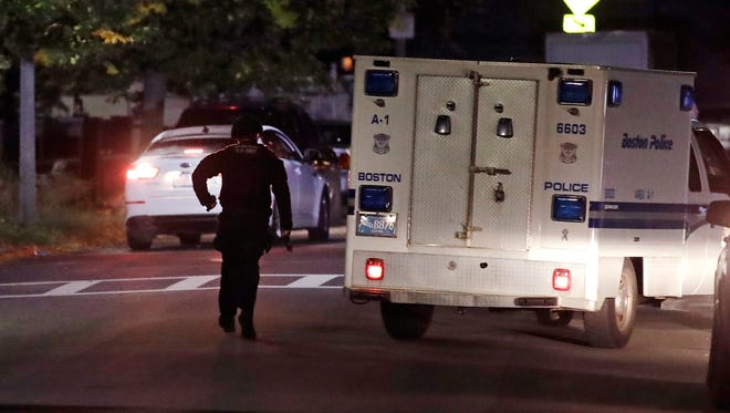 Police search for a suspect after a police shooting in the East Boston neighborhood of Boston, Wednesday, Oct. 12, 2016.