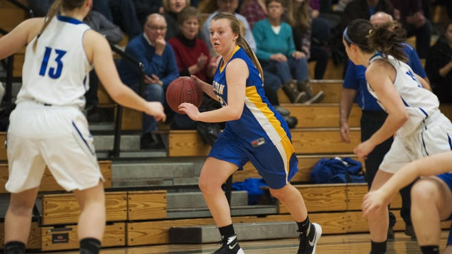 Milton's Cassidy Button (21) dribbles the ball down the court during a high school girls basketball game between the Milton Yellowjackets and the Colchester Lakers.