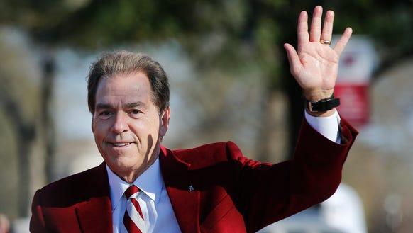Alabama's coach Nick Saban waves to fans as he parades