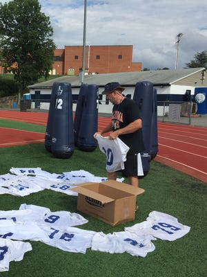 Assistant coach Mike Lyons lays out Randolph football jerseys on the first day of NJSIAA-approved practice.