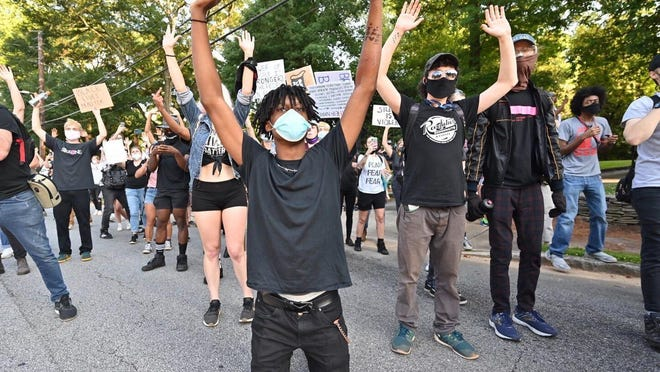 People line the street in front of the Governor's Mansion as protests began for a second day over the death of George Floyd on Saturday, May 30, 2020 in Atlanta.