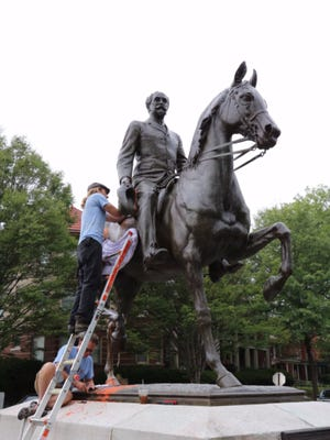 A crew removes paint from the Castleman statue in the Highlands. The process to remove the paint will take about a week.