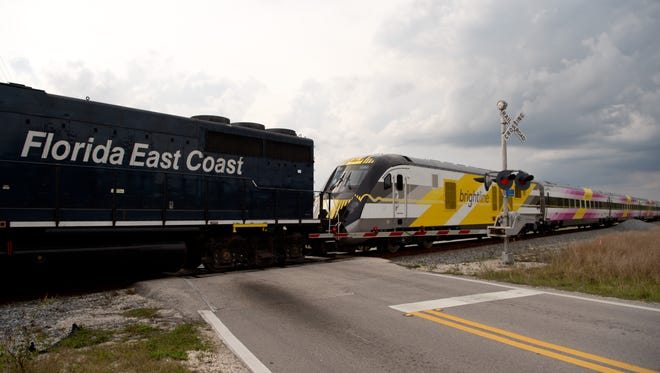 A Brightline passenger train, pulled by a Florida East Coast engine, moves south past the Walton Road crossing March 13, 2017, in Port St. Lucie.