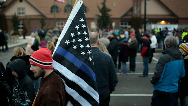 A U.S. flag with the red and blue colors replaced with black, and with a blue line replacing the white line immediately below the field of stars, is known as the Thin Blue Line flag. The flag shows support for police officers. Richard Machnik, of Westerville, holds a Thin Blue Line flag before a community vigil for fallen Westerville Police officers Eric Joering and Anthony Morelli on Tuesday, February 13, 2018 at First Responders Park in Westerville, Ohio.