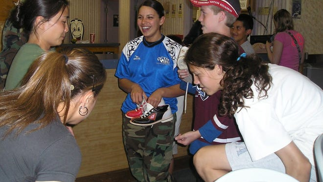 In this 2007 file photo from Holloman Air Force Base, Airman 1st Class Cindy Ventura, 49th Aeromedical Dental Squadron, chats with members of the Holloman Air Force Base soccer team at the Desert Lanes Bowling Alley.