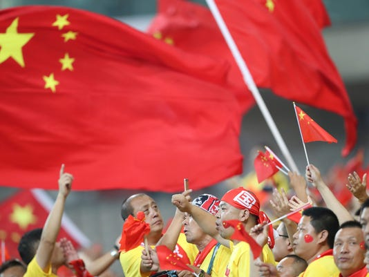 Supporters of the China national soccer team wave their national flags during the soccer match against South Korea for the 2018 FIFA World Cup qualifier at Seoul World Cup Stadium in Seoul, South Korea, Thursday, Sept. 1, 2016. (AP Photo/Lee Jin-man)