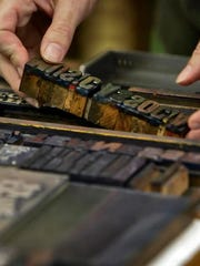 An employee moves collection of lead type at Hatch Show Print.