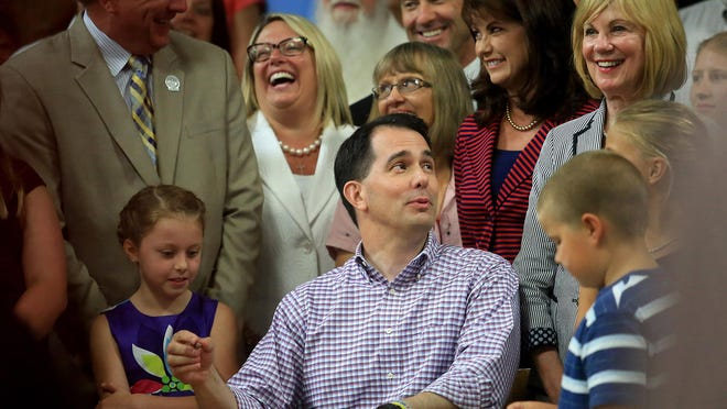 Wisconsin Gov. Scott Walker converses with attendees while signing the state's 2015-2017 budget during a ceremony Sunday on the production floor of Valveworks USA in Waukesha.