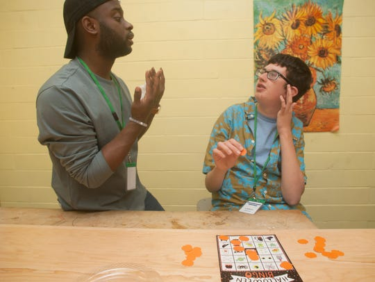 T.J. Copeland works with SMASH program student Christopher Heitzman during a bingo game at the Moorestown Recreation Center.