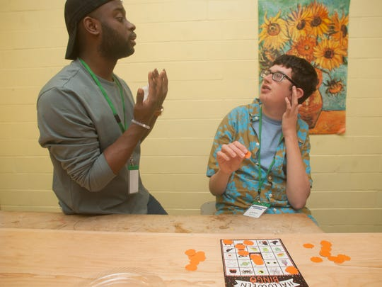 T.J. Copeland, center, works with SMASH program students, Christopher Heitzman, during a bingo game at the Moorestown Recreation Center.