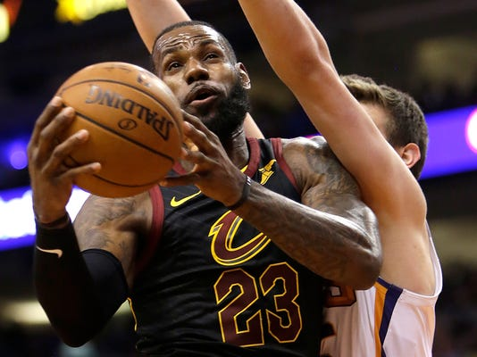 Cleveland Cavaliers forward LeBron James (23) gets fouled by Phoenix Suns forward Dragan Bender in the first half of an NBA basketball game, Tuesday, March 13, 2018, in Phoenix. (AP Photo/Rick Scuteri)