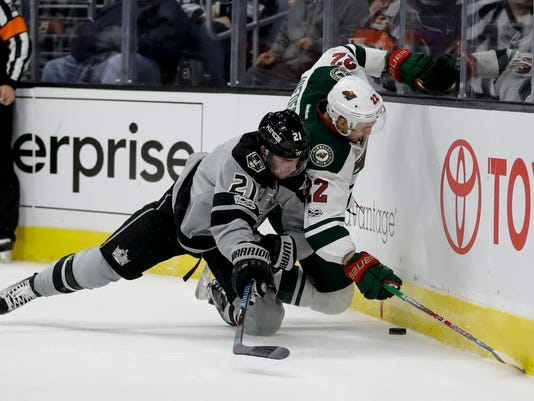 Los Angeles Kings center Nick Shore, left, and Minnesota Wild right wing Nino Niederreiter vie for the puck during the first period of an NHL hockey game in Los Angeles, Saturday, Jan. 7, 2017. (AP Photo/Chris Carlson)