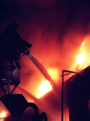 Firefighter douses a fire with water.