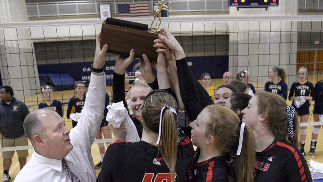 Penfield girls volleyball coach Andrew Solomon, left, and the Patriots lifting the Section V Class AA championship trophy in November of 2016.