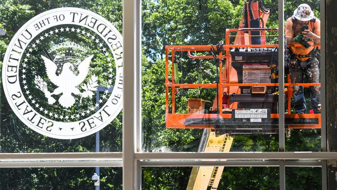A worker from outside takes a view inside after the presidential seal has been affixed on the new main entrance of Truman Library & Museum. Library officials still plan to reopen the building in the fall.