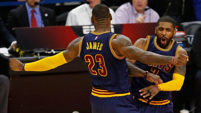 Kyrie Irving #2 of the Cleveland Cavaliers celebrates his late fourth quarter three pointer with LeBron James #23.