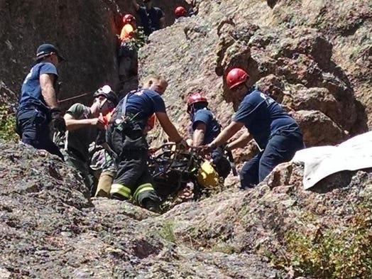 Emergency personnel work to remove an injured hiker from Horsetooth Rock on Monday morning.