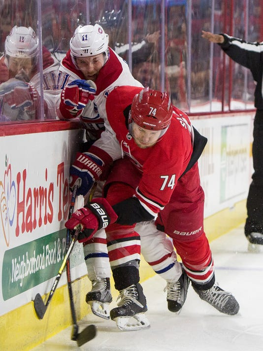 Montreal Canadiens' Brendan Gallagher (11) and Carolina Hurricanes' Jaccob Slavin (74) collide along the boards during the first period of an NHL hockey game in Raleigh, N.C., Thursday, Feb. 1, 2018. (AP Photo/Ben McKeown)