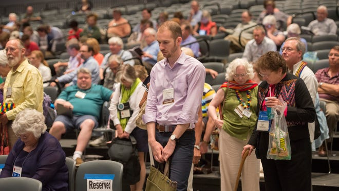 The audience takes part in an opening prayer at the 221st General Assembly of the Presbyterian Church at Cobo Hall in Detroit on June 19, 2014.