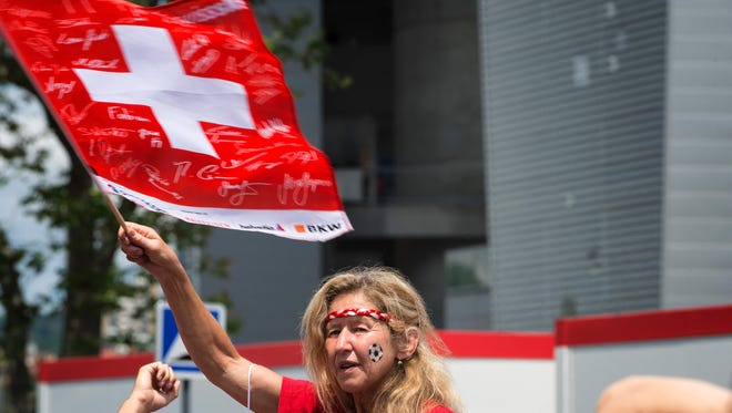 A Switzerland supporter holds a Swiss flag in Saint-Etienne, France, before the Euro 2016 soccer match between Switzerland and Poland on June 25, 2016.