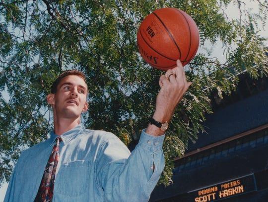 First-round draft pick Scott Haskin spins a basketball