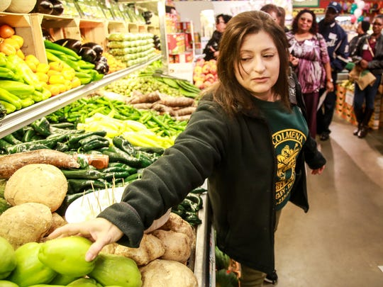 Manager Irene Huddleston talks to shoppers about the Mexican produce they sell during the Green Grocer Project grocery store crawl at Honey Bee Market in southwest Detroit on Saturday, Nov. 14, 2015.