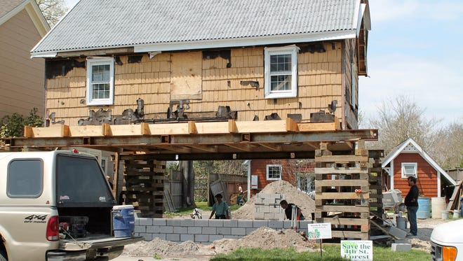 Workers rebuild the foundation for one of the historic homes lifted off of its foundations on Mulberry Street in Lewes. The number from the house has been removed from the house. Many of the homes on Mulberry Street date back to colonial times.