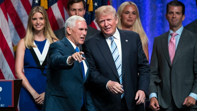 Republican presidential candidate Donald Trump (right) talks with Gov. Mike Pence after today's campaign event in Manhattan to announce Pence as Trump's vice presidential running mate.