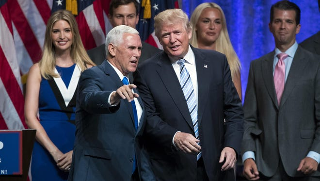Republican presidential candidate Donald Trump talks with Gov. Mike Pence during a campaign event on July 16, 2016, in New York.