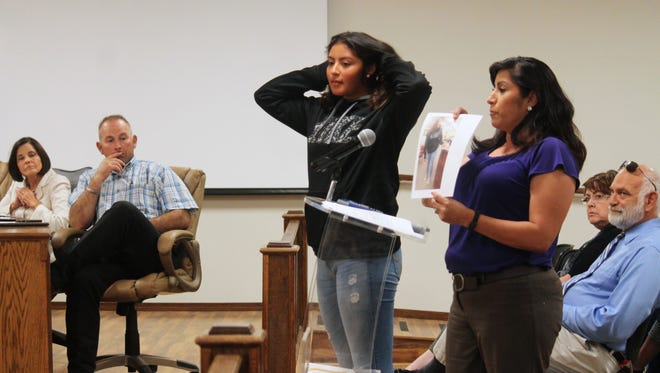 Eliza Fernandez shows the Alamogordo Board of Education what her daughter, Isabel, was wearing when Alamogordo High School Principal George Heaton deemed her jeans inappropriate and pulled her out of class.