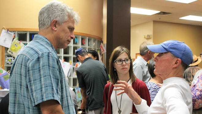 Jeff Stant, Alayna Pierce and Hugh Baker talk after a public meeting hosted by the Indiana Forest Alliance Wednesday night. Attendees discussed their frustrations with the decision to build a memorial in the north woods of Crown Hill Cemetery.